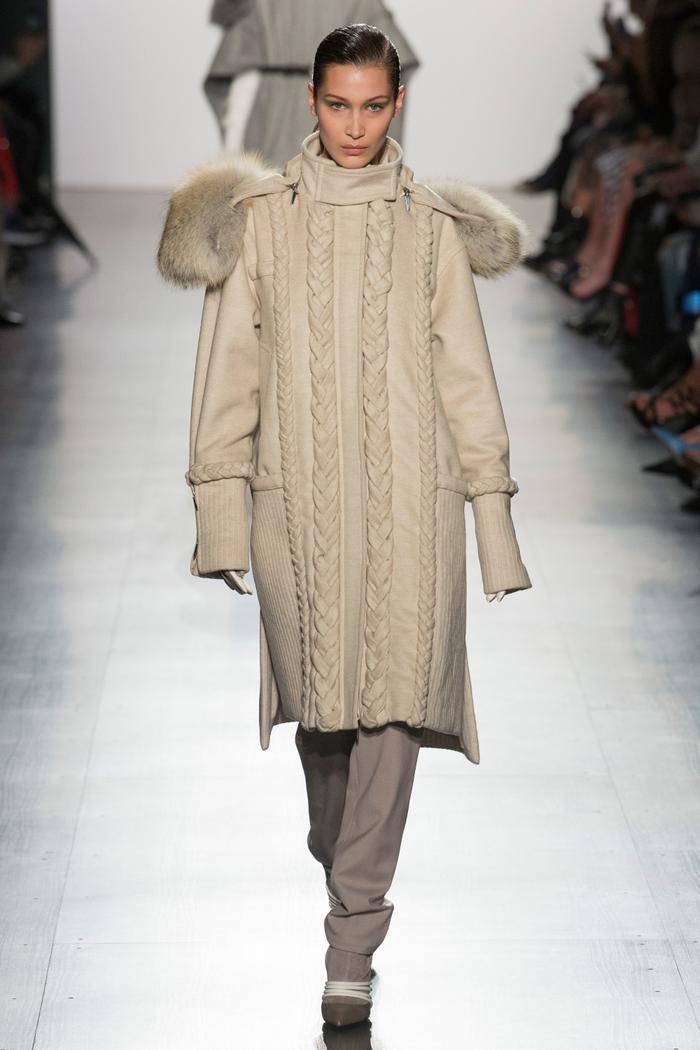 Bella Hadid mở màn buổi trình diễn trong thiết kế áo khoác lạ lẫm với họa tiết vặn thừng nổi. Mẫu áo cổ cao lấy cảm hứng từ áo khoác trượt tuyết của những người dân vùngBắc Ireland.