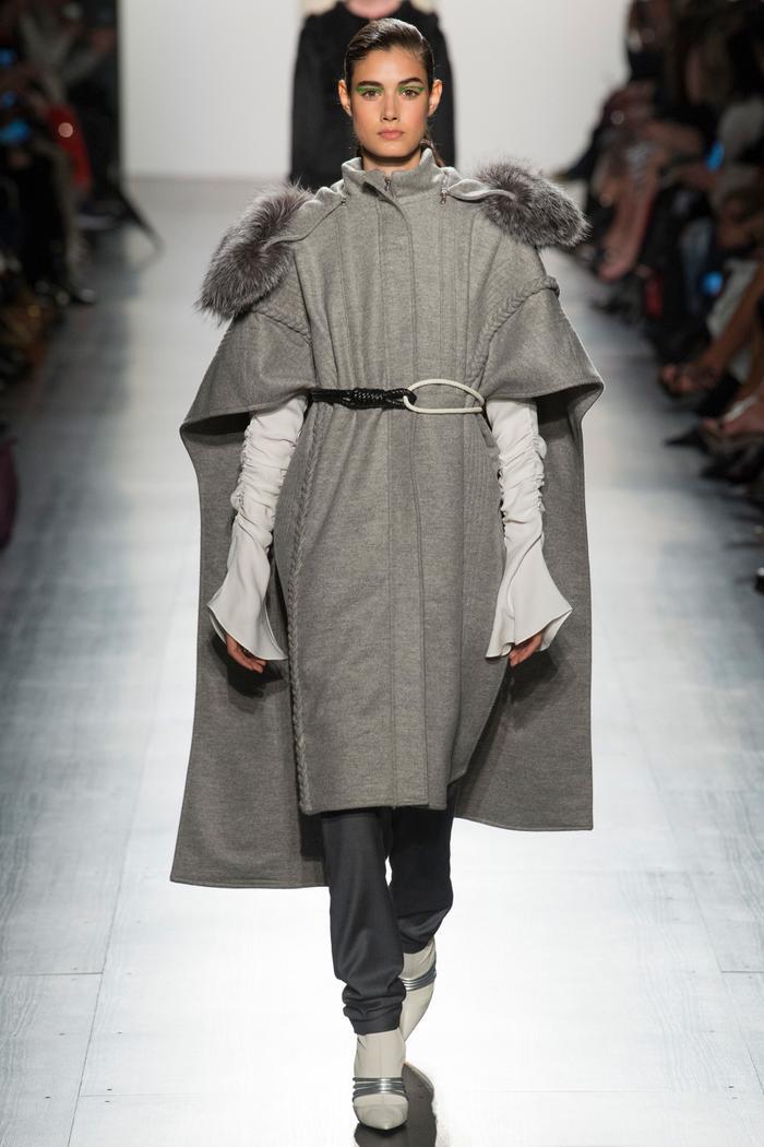 Chiếc áo cape mang bóng dáng của chàng kỵ sĩ ngự lâm được mềm mại hóa bằng chất liệu vải và thiết kế đính lông hai bên cầu vai.