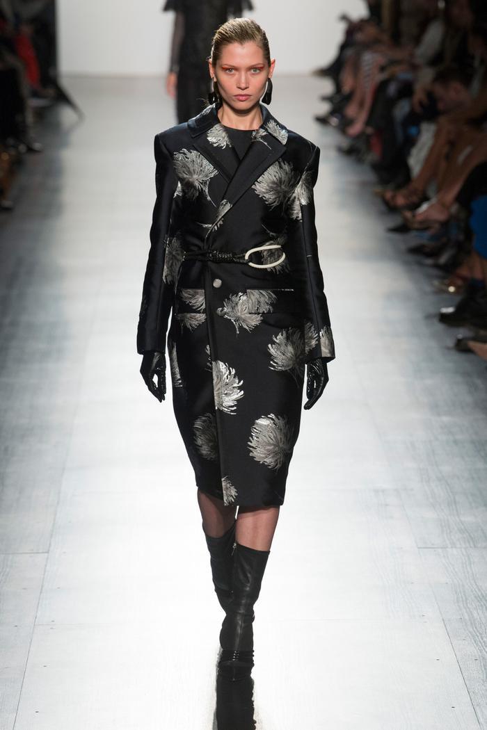 Mẫu áo khoác mang sự kết hợp giữa áo blazer và trench coat. Màu đen lụa làm tăng sự sang trọng, bóng bẩy. Họa tiết trên áo lấy cảm hứng từ đóa hoa cúc mộc mạc và giản dị.