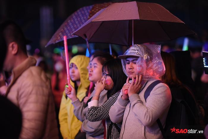 Khi chương trình bắt đầu khoảng 30 phút, trời bắt đầu mưa nặng hạt. Mọi thứ được các fan tận dụng để che chắn.