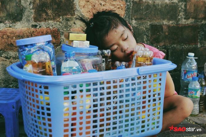 Một em bé say sưa ngủ bên quán trà của mẹ. Tuổi thơ em lớn lên bên gánh hàng nước và những giấc bên quán trà ven đường.