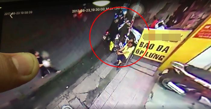 Hai người đi xe máy giả vờ hỏi đường để đánh lạc hướng. Ảnh chụp từ clip
