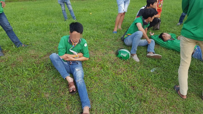 3 nạn nhân nằm vật vã trên bãi cỏ sau khi bị hành hung.