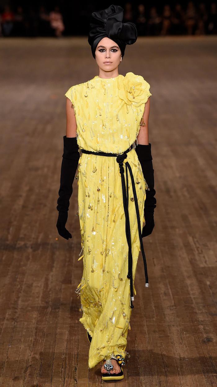 """Kaia Gerber Kaia đã """"đóng khung"""" trong chiếc váy đính hạt màu vàng tươi với đóa hoa lớn ở vai. Sự kết hợp giữa sắc vàng trang phục và sắc đen phụ kiện từ đôi găng tay dài đếnchiếc khăn che dấu mái tóc đã mang đến cho gương mặt đại diện nước hoa của hãng trở nên nổi bật hơn rất nhiều."""