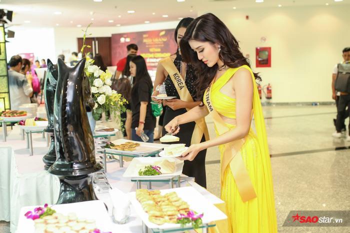 Á hậu Việt Nam 2014 cũng tranh thủ nhờ đại diện Hàn Quốc cùng mình làm công việc này để có thể mang nhiều phần thức ăn hơn cho các người đẹp khác.
