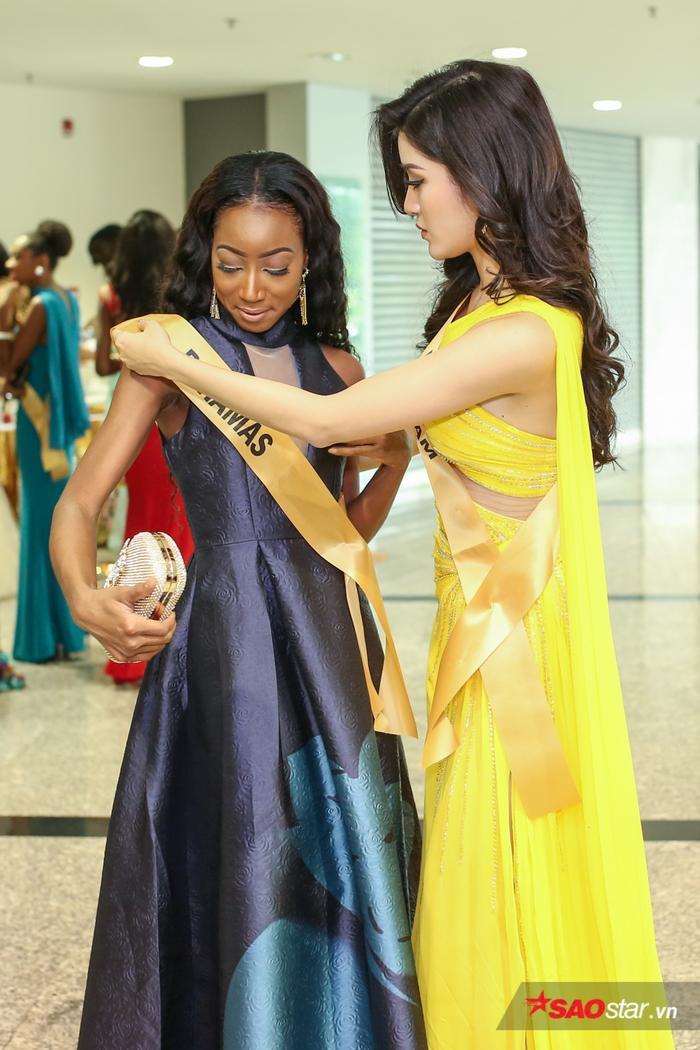 Một khoảnh khắc đẹp khác khi Á hậu Huyền My ân cần chỉnh lại trang phục cho Miss Bahamas.
