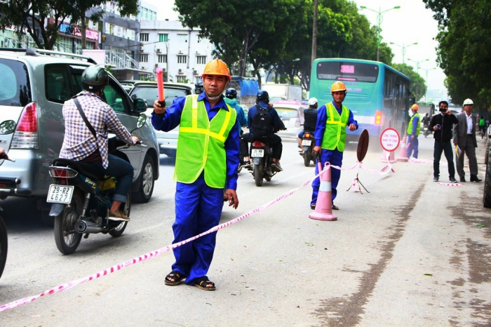 Để đảm bảo cho việc chặt, cắt tỉa cành cây, ban quản lý dự án đã huy động nhiều công nhân tổ chức phân luồng giao thông, căng dây chắn.