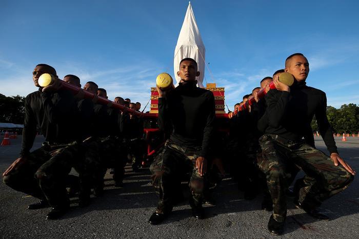 Đoàn khiêng bình tro cốt tượng trưng tập dượt trước sự kiện. Ảnh: Reuters.