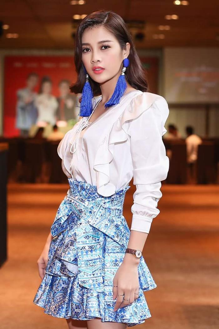Chân váy bèo áp dụng kỹ thuật 3D bất đối xứng phối cùng kiểu áo tay bồng dựng form gam màu trắng mang đến cái nhìn thanh thoát cho Mỹ Duyên. Hoa tai tua rua bắt mắt cũng góp phần đem lại sự thú vị, phá cách cho tổng thể.
