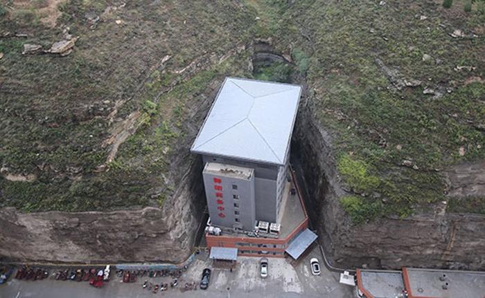 """Một công trình kiến trúc khác cũng khiến nhiều người phải cảm thán. Khách sạn có tám tầng và được xây dựng từ năm 2016 tại tỉnh Thiểm Tây, Trung Quốc. Độ độc và lạ của khách sạn chính là ở vị trí xây dựng có chút bất thường. Nó """"mọc"""" giữa khoảng trống của hai vách đá cao sừng sững. Đó cũng chính là lý do vì sao rất nhiều người gọi khách sạn này là """"Roujiamo""""- món humburger của Trung Quốc."""