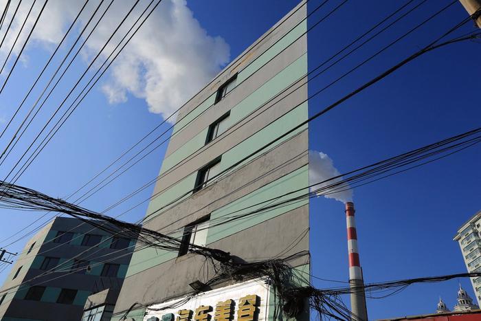 """Ngày 19/11, hình ảnh của tòa nhà kỳ lạ ở Cáp Nhĩ Tân, thủ phủ của tỉnh Hắc Long Giang, Trung Quốc đã gây ấn tượng mạnh đối với giới kiến trúc sư nói riêng và người dân nói chung. """"Tòa nhà A4"""" cao năm tầng, được sơn hai màu xám và bạc. Điều kỳ lạ của công trình này là nếu như nhìn từ góc nghiêng, chúng ta sẽ có cảm giác nó mỏng như một tờ giấy, còn nếu như đứng ở phía trực diện thì nó lại giống quyển sách vậy."""