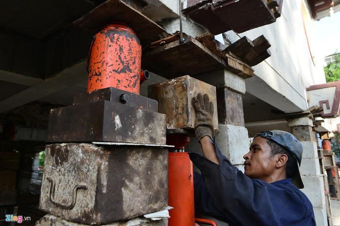 Các công nhân luôn phải điều chỉnh kích thủy lực bằng tay và đế kê.