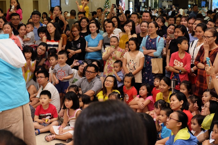 Hàng trăm em nhỏ được bố mẹ đưa đi chơi lần đầu nhìn thấy thần tượng của mình. Các bé ổn định chỗ ngồi và xem Huỳnh Lập biểu diễn.
