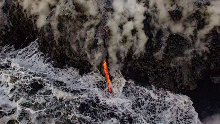 Trên những sườn núi của Kilauea Volcano, Hawai'i, lối vào biển dung nham lớn nhất thế giới. Sau khi phun trào vào đầu năm 2016, dòng chảy dung nham mất khoảng hai tháng để chảy sâu xuống biển. Hình ảnh của Greg C. đứng ở vị trí thứ ba trong thể loại Trên không.