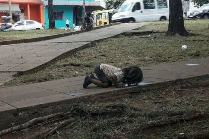 Cô bé đang quỳ gối uống nước từ một vũng nước bẩn bên đường.