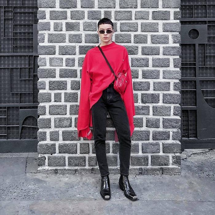 """Stylist Kelbin lại là một hình tượng cá tính tuyệt đối. Lựa chọn áo thun tay dài được đóng thùng cách bất đối xứng, anh chàng chứng tỏ khả năng mix đồ cao tay khi phối chiếc áo phom rộng cùng với quần skinny jeans và boots khiến vóc dáng có phần bé nhỏ cuả anh không hề bị """"nuốt chửng"""" trong trang phục. Bên cạnh đó, chiếc túi đeo chéo cùng màu áo đã """"hoàn thành sứ mệnh"""" trở thành điểm nhấn đắt giá trong set đồ."""