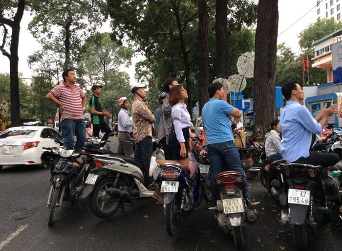 Người dân đứng từ ngoài đường, trèo lên xe máy để theo dõi bóng đá.