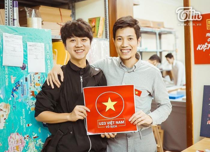 Anh Vũ Vinh Trà (bên phải) tặng hình dán miễn phí cho cổ động viên để cổ vũ tinh thần U23 Việt Nam