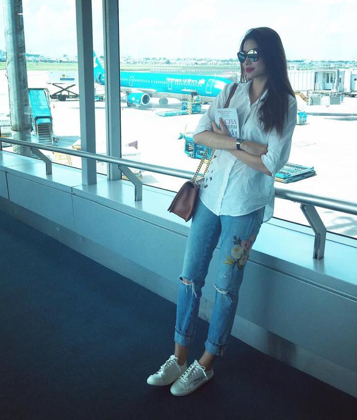 Thời trang sân bay của hoa hậu diện chiếc quần jeans rách thêu cực trẻ trung với áo sơ mi trắng đơn giản.