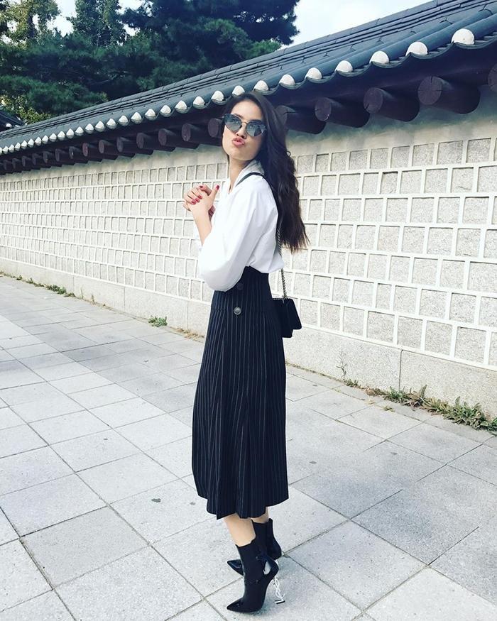 """Có khi Phạm Hương lại """"đổi gió"""" bằng một chiếc chân váy kẻ điệu đà, kết hợp cùng đôi boot đen tôn dáng."""