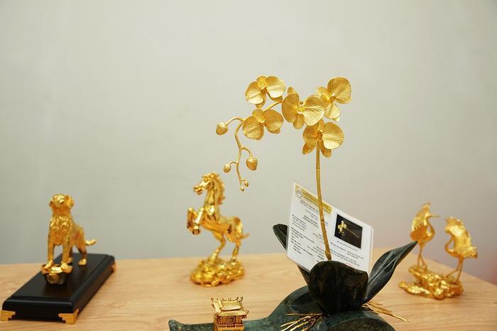 """Chậu hoa lan đặc biệt này có 2 phiên bản được chế tác từ 100 đến 200 chỉ vàng 24K. Phiên bản thứ nhất toàn bộ cành, hoa, nụ được đúc từ 10 lượng vàng, toàn bộ lá của chậu lan được chế tác từ ngọc xanh tự nhiên. Đây là phiên bản """"Cành vàng lá ngọc""""."""