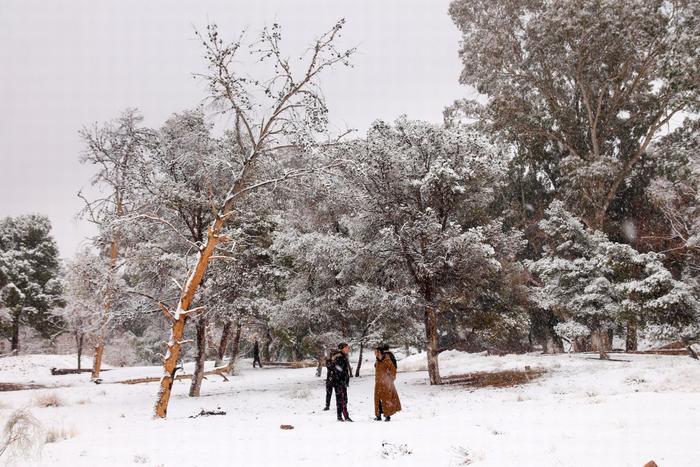 Các du khách lang thang ngắm cảnh tuyết rơi tại sa mạc nóng nhất thế giới.