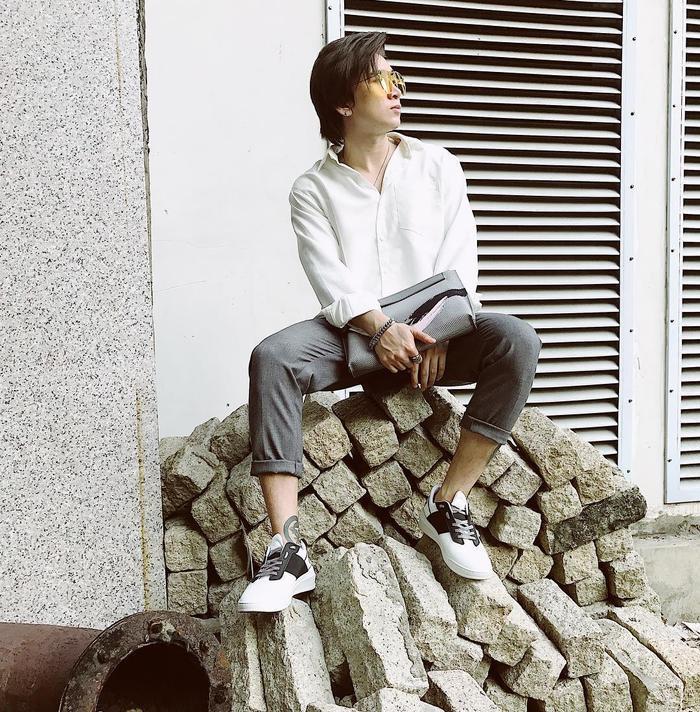 Sơ mi trắng cùng quần tây là trang phục mà Chi Dân lựa chọn khi xuống phố mùng 3 Tết. Anh chàng tự cộng thêm điểm cho set đồ với những phụ kiện như giày sneaker, kính mát trong cùng clutch cầm tay Pedro.