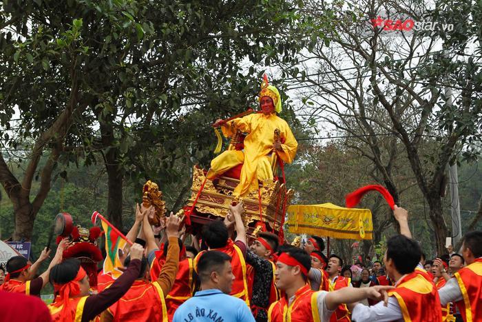 """Sau khi """"vua"""", """"chúa"""" cùng bá quan yên vị, yến tiệc bắt đầu; tan tiệc trống chiêng nổi lên rộn rã, theo nghi lễ truyền thống, """"chúa"""" lên kiệu vào yết """"vua"""", sau đó """"vua"""" lên kiệu và cuộc rước bắt đầu: """"vua"""" lên bái vọng đức Huyền Thiên ở đền Sái và thực hiện nhiều nghi lễ khác ở đình, chùa. Ảnh: Thế Việt."""