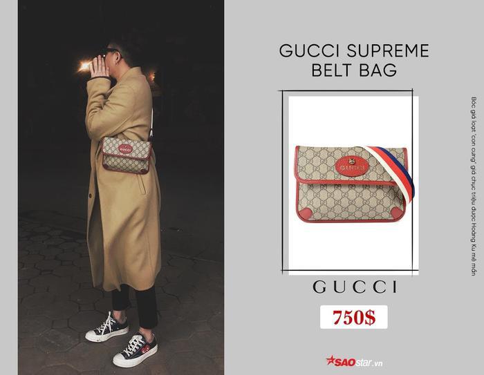 """Chiếc túi đánh dấu sự hợp tác của Gucci cùng nhà mốt chuyên trị mảng street wear Supreme. Với thiết kế dây tăng-đơ tiện lợi, có thể tùy chỉnh độ dài của quai đeo, sản phẩm này được cho là có thể dễ dàng biến hóa từ túi đeo chéo, đến túi ngang hông. Ngoài ra, gam màu đỏ như Hoàng Ku sử dụng cũng chỉ được sản xuất tại châu Á, điều đó khiến nó trở thành một items """"hiếm có, khó tìm"""". Giá để sở hữu món phụ kiện này là 750$, hơn 17 triệu đồng."""