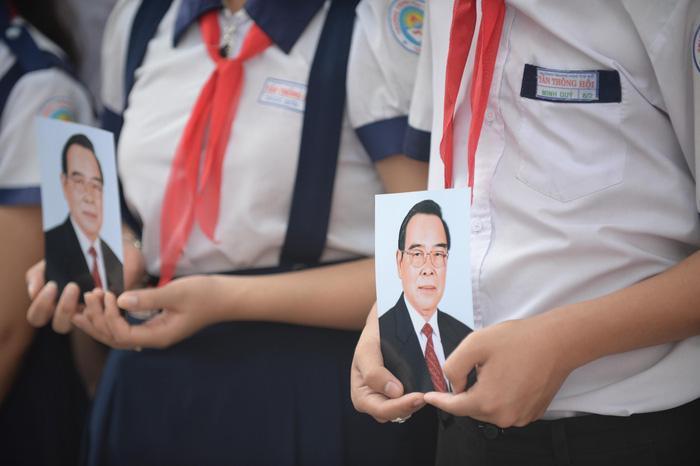 Các em học sinh xã Tân Thông Hội mang theo ảnh ông Sáu Khải chờ đón ông tại nhà - Ảnh: THUẬN THẮNG