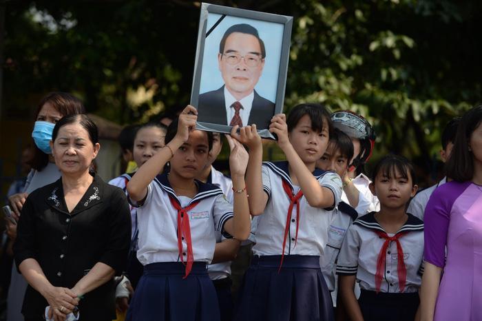 Người dân mang ảnh cố Thủ tướng Phan Văn Khải đứng chờ đón đoàn xe tang của ông đi qua trên đường về Củ Chi - Ảnh: THUẬN THẮNG.