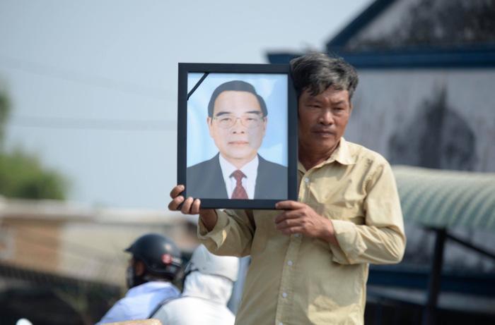 Người dân mang ảnh cố Thủ tướng Phan Văn Khải đứng chờ đón đoàn xe tang của công đi qua trên đường về Củ Chi - Ảnh: THUẬN THẮNG.