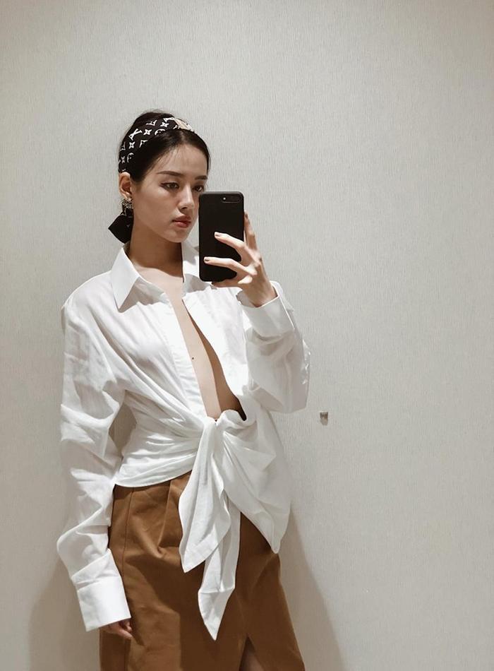 Áo buộc vạt cũng đang được các cô gái rất yêu thích. Khánh Linh chọn kết hợp màu trắng và nâu, hai gam màu đi với nhau luôn đảm bảo đẹp.