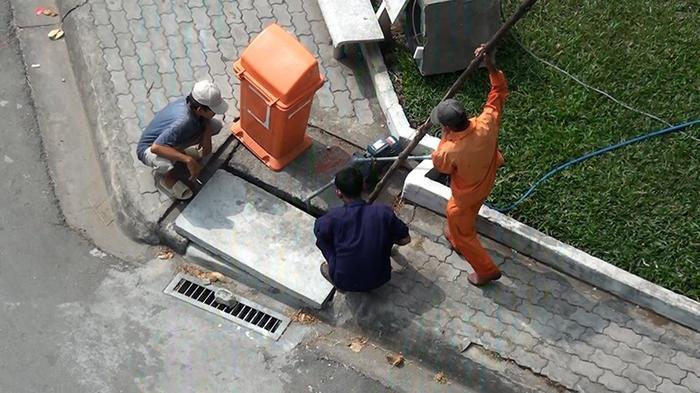 Hai công nhân nạy nắp cống hố ga để lấy nước tưới Công viên Lý Chiêu Hoàng (quận Bình Tân, TP.HCM). Ảnh: NGUYỄN TÂN