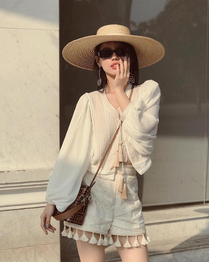 Khánh Linh The Face lại đem đến chút không khí du mục gồm áo kiểu và quần tua rua chất linen, đi kèm phụ kiện mũ cói bản to.
