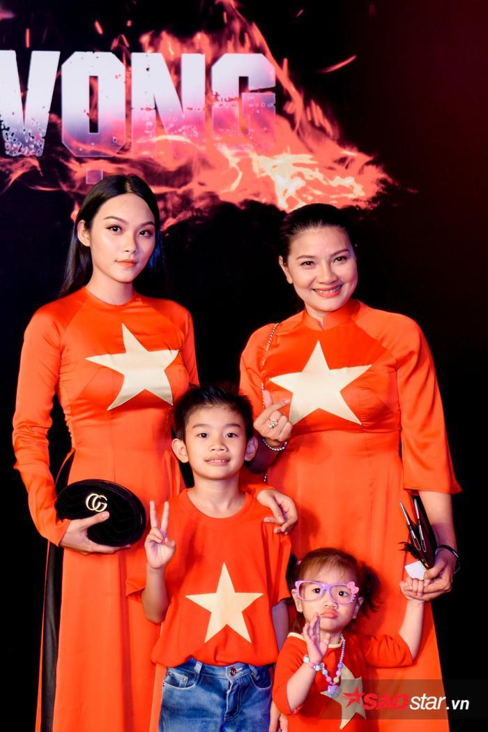 Hai mẹ con diễn viên Kiều Trinh và Thanh Tú diện trang phục áo dài có in cờ Việt Nam.