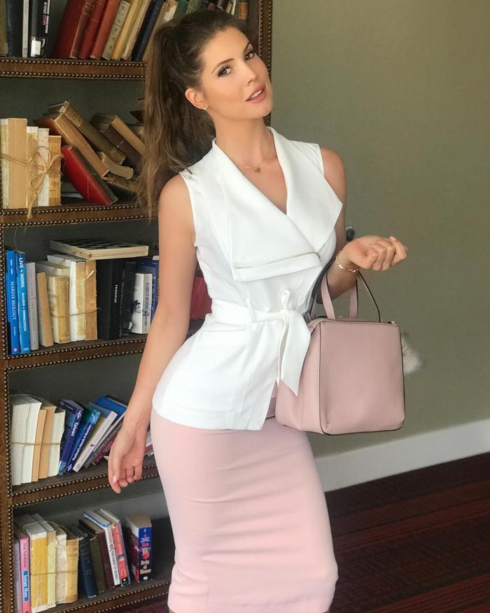 Set đồ với áo sơ mi không tay cách điệu nhấn nhá bằng dây cột eo cùng chân váy hồng bó sát khoe triệt để vòng eo con kiến, thêm một chiếc túi xách thiết kế tinh giản là chuẩn cho 1 cô nàng công sở điệu đà.