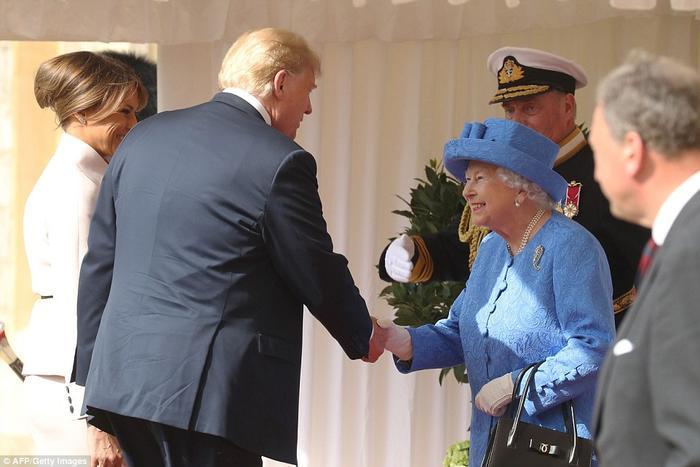 Nữ hoàng trông không vui bởi sự chậm trễ, thậm chí còn kiểm tra đồng hồ khi đứng đợi ông Trump và Đệ nhất phu nhân Melania. Và khi chiếc Range Rover màu đen của vợ chồng Tổng thống Mỹ tới Lâu đài Windsor, ông Trump gần như ngay lập tức vi phạm giao thức hoàng gia. Ông Trump đã phá vỡ truyền thống bằng cách không cúi chào Nữ hoàng, thay vào đó là bắt tay. Đệ nhất phu nhân Melania cũng làm tương tự như phu quân. Ảnh: AFP/Getty