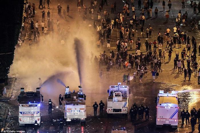 … buộc cảnh sát phải dùng vòi rồng để giải tán đám đông. Khoảng 4.000 cảnh sát và lực lượng an ninh đã được triển khai trên khắp Paris trong mùa World Cup và một vành đai an ninh lớn cấm xe cộ đã được thiết lập quanh đại lộ Champs Elysees. Ảnh: AFP/Getty