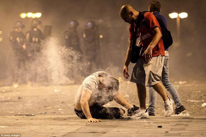 Một thanh niên ngồi gục xuống đất do hít phải hơi cay khi cảnh sát đụng độ các cổ động viên quá khích. Ảnh: Getty