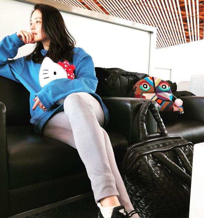 Thư Kỳ chọn áo freesize màu sáng và quần jeans đơn giản khi đi du lịch.