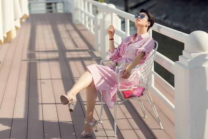 Chiếc váy sơ mi dọc trắng đỏ với phần eo xoắn độc lạ được Thu Phương kết hợp cùng sandals và túi trong suốt mới thời thượng làm sao.