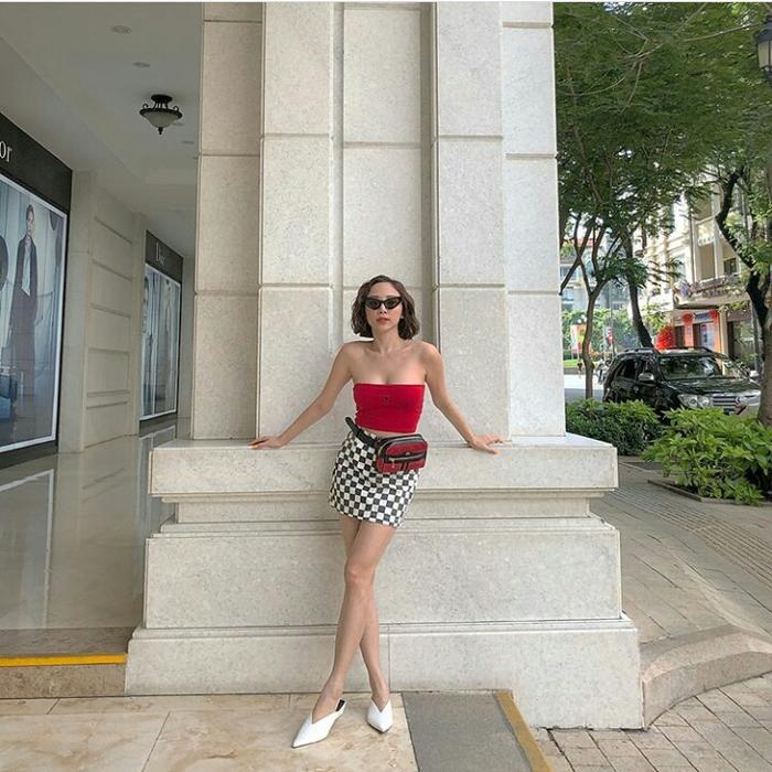 Người đẹp khéo léo phối áo quây đỏ cùng chân váy caro và túi đeo hông nhấn nhá sành điệu với kính mắt mèo, toàn những món đò cực trendy giúp cô nổi bật, thu hút trên phố.