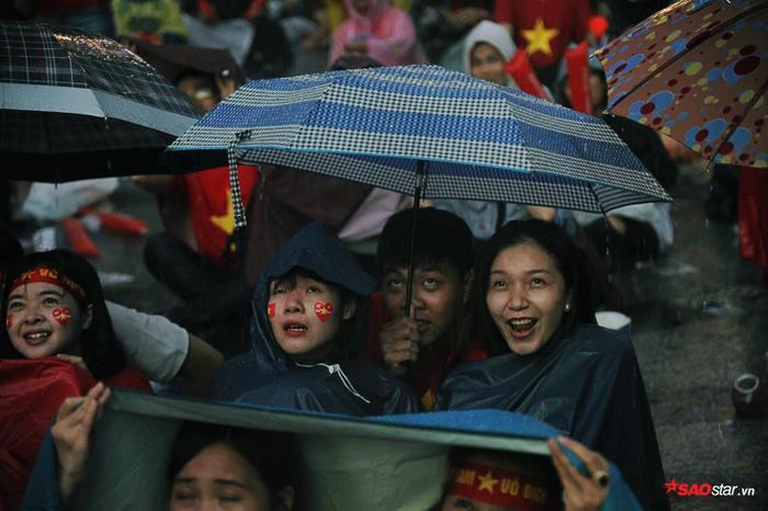 Một chiếc áo mưa được 3 cổ động viên trú chung.