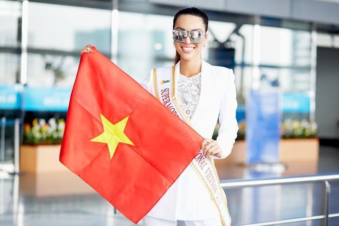 Siêu mẫu Khả Trang thể hiện sự tự tin khi cầm Quốc Kỳ Việt Nam giương cao tại sân bay.