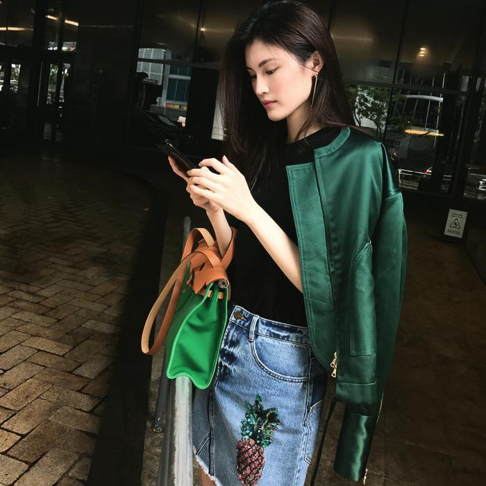 """Tô điểm cho chiếc áo thun đen trơn bằng một chiếc váy denim họa tiết hình trái thơm và chiếc áo khoác màu xanh lá """"ton sur ton"""" với chiếc túi xách"""