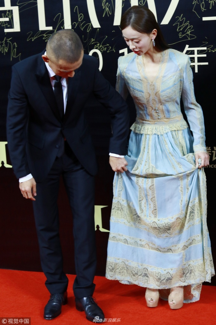 Giúp nữ diễn viên chỉnh lại trang phục.