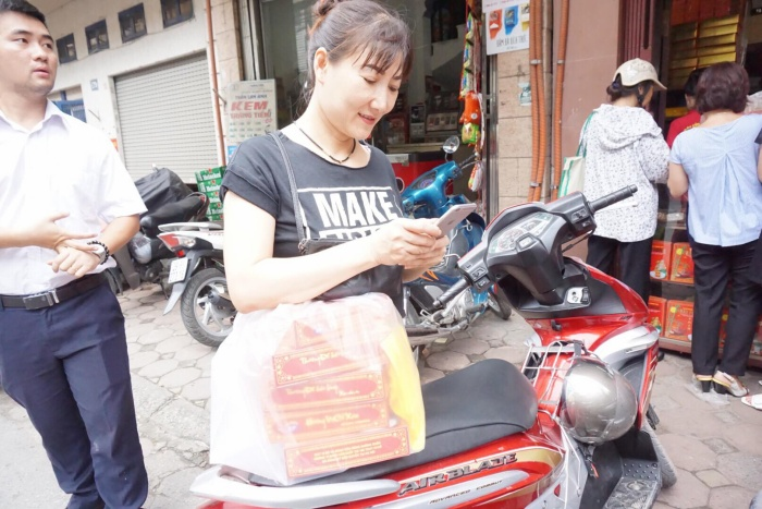 Chị Hà (ở phường Ngọc Thuỵ, quận Long Biên) vui vẻ vì sau hơn 1 giờ đồng hồ xếp hàng chị cũng đã mua được những hộp bánh trung thu.