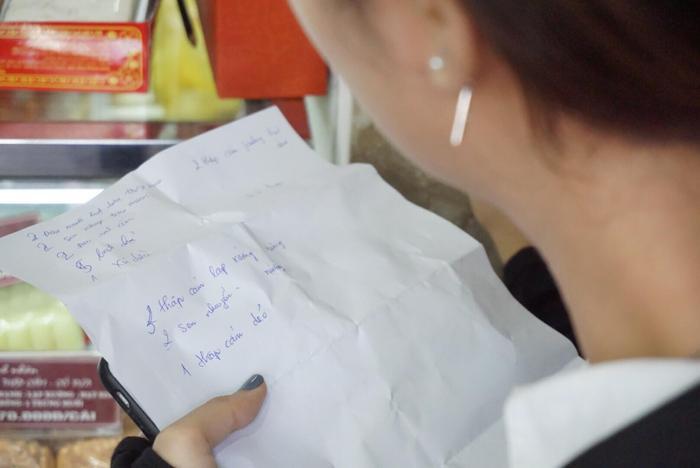 Nhiều người cẩn thận ghi từng loại bánh trung thu khi đến cửa hàng.