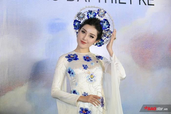 Khoác lên mình bộ áo dài màu trắng với những hoạ tiết hoa màu xanh được in nổi bật trên nền lụa, kết hợp cùng chiếc mấn cầu kỳ, Huyền My khiến người xem không thể rời mắt.